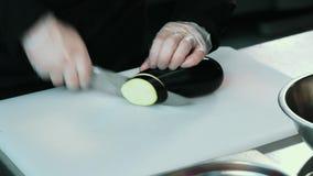 Fachowy szef kuchni szybko ciie oberżyny na białej desce używa nóż Zakończenie zbiory