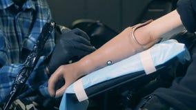 Fachowy tattooer pracuje na bionic ręce niepełnosprawna osoba, tatuażu wyposażenie zbiory