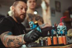 Fachowy tatuażu artysta robi nowemu tatuażowi dla jego klienta obrazy royalty free