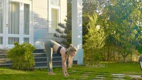 Fachowy występ asana joga młodą dziewczyną przy podwórkem jej dom zdjęcie stock