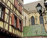 Fachwerk- Haus und Kirche mit schönem kopiertem Ziegeldach - Colmar, Frankreich stockbild