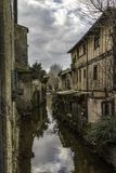 Fachwerk house on a canal in Mirepoix. Traditional fachwerk houses near canal in early springtime. South of France. Mirepoix Royalty Free Stock Photography