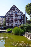 Fachwerk house. OCHSENWANG, GERMANY - CIRCA AUGUST 2015 Fachwerk house near green pond Stock Photo