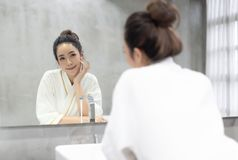 Facial Beauty.Beautiful smiling young Asian woman in bathrobe applying moisturizer cream on her pretty face and looking to mirror. At bathroom, touching face royalty free stock images