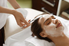 Facial Beauty Treatment. Beautiful Woman Getting Cosmetic Mask Stock Image