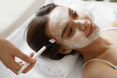 Facial Beauty Treatment. Beautiful Woman Getting Cosmetic Mask Royalty Free Stock Photography