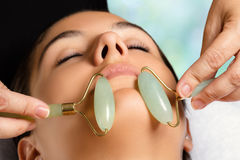 Facial beauty treatment with jade rollers. Macro close up portrait of woman having facial beauty treatment in spa. Therapist massaging chin with jade rollers Royalty Free Stock Photo