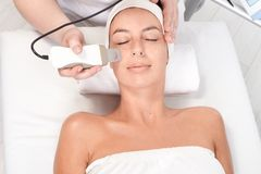 Facial beauty treatment. Young woman laying eyes closed, getting facial beauty treatment, view from above royalty free stock photo