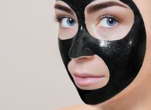 Facial black Mask  to the face of a beautiful woman. Spa treatments and care of the cats in the beauty salon Stock Image