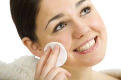Facial care. Young woman taking care about her face holding a cotton pad Royalty Free Stock Image