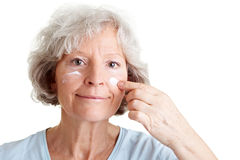 Facial care for elderly woman Stock Images
