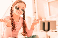 Positive joyful girl sitting with black eye patches on her face stock images