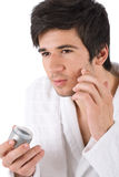 Facial care - Young man applying moisturizer Stock Photos