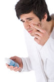 Facial care - Young man cleaning face with lotion Stock Image