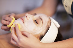 Facial cleaning. Woman in spa with facial mask Stock Images
