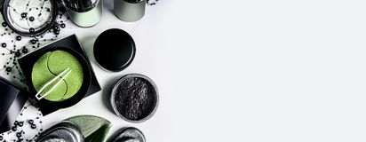 Facial cosmetic products set in black and brown packaging. Natural cosmetics. Modern skin care with eye patch and charcoal powder. On light background, top view royalty free stock image