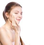 Facial cream. Beautiful woman applying facial cream Stock Image