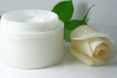 Facial cream. Close-up of a face cream with white rose on top stock photo
