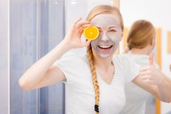 Happy young woman having face mask holding kiwi. Facial dry skin and body care, complexion treatment at home concept. Happy young woman having grey mud mask on Royalty Free Stock Photo
