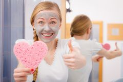 Woman having grey face mask holding heart sponge. Facial dry skin and body care, complexion treatment at home concept. Happy young woman loving having grey mud Stock Image