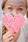 Woman having grey face mask holding heart sponge. Facial dry skin and body care, complexion treatment at home concept. Happy young woman loving having grey mud Royalty Free Stock Image