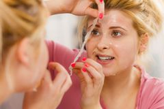 Woman peeling off gel mask from face Stock Photography
