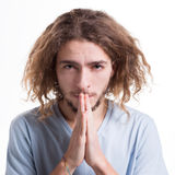 Facial expression and emotion, Hopeful man praying. Facial expression and emotions. Begging man praying, holding hands clasped near face on white isolated studio Stock Photography