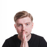 Facial expression and emotion, Hopeful man praying. Facial expression and emotions. Begging man praying, holding hands clasped near face on white isolated studio Royalty Free Stock Photo