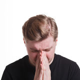 Facial expression and emotion, Hopeful man praying. Hopeful man praying, holding hands clasped near face on white isolated studio background Stock Images