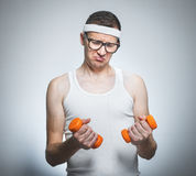 Facial expression nerd with dumbbells stock photography