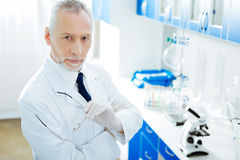 Serious medical worker posing in the laboratory. Facial expressions. Delighted practitioner holding his glasses and crossing arms while looking forward royalty free stock photos