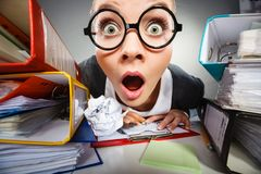 Crazy thoughtful accountant businesswoman. Facial expressions during work. Crazy thoughtful accountant businesswoman surrounded by documents and binders in royalty free stock images