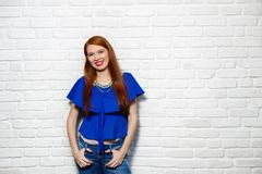 Facial Expressions Of Young Redhead Woman On Brick Wall. Portrait of happy white woman smiling. Caucasian redhead girl laughing and looking at camera. Copy space Stock Photo