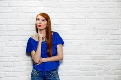 Facial Expressions Of Young Redhead Woman On Brick Wall. Portrait of puzzled woman having doubts, doubtful redhead girl thinking. Youth culture with female teen Royalty Free Stock Photo