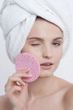 Facial funny portrait young lady with natural make up. French manicure and clear skin with white towel on her head and pink rough sponge in her left hand Royalty Free Stock Photography
