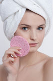 Facial funny portrait young lady with natural make up. French manicure and clear skin with white towel on her head and pink rough sponge in her left hand Royalty Free Stock Photo