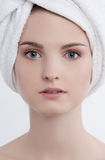 Facial funny portrait young lady with natural make up. French manicure and clear skin with white towel on her head and pink rough sponge in her left hand Royalty Free Stock Image