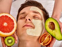 Facial mask from fresh fruits for man . Beautician apply slices. Facial mask from fresh fruits and clay for man. Beautician apply slices of avocado, grapefruit stock photography