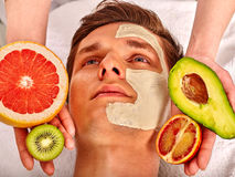 Facial mask from fresh fruits for man . Beautician apply slices. Royalty Free Stock Images