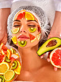 Facial mask from fresh fruits for woman . Beautician apply slices. Royalty Free Stock Images