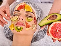Facial mask from fresh fruits for woman . Beautician apply slices. Facial mask from fresh fruits for woman. Beautician apply slices of avocado, grapefruit stock photos