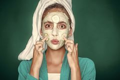 Facial mask. Girl face with kiss lips, cucumber mask on green background. Woman with bath towel on head. Skin and hair care, spa, wellness. Rejuvenation stock images