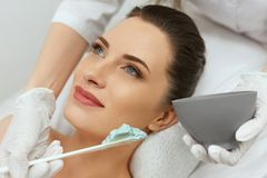 Facial Mask. Woman Applying Cosmetic Alginate Mask On Skin royalty free stock image