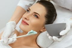 Facial Mask. Woman Applying Cosmetic Alginate Mask On Skin stock photography