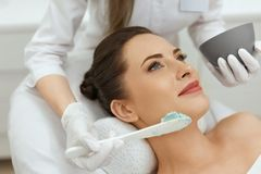 Facial Mask. Woman Applying Cosmetic Alginate Mask On Skin royalty free stock photos