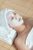Facial mask for the young lady at spa. A young lady enjoying facial mask at spa, at beauty salon, indoors Stock Photography