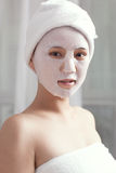 Facial mask for the young lady at spa. A young lady enjoying facial mask at spa, at beauty salon, indoors Royalty Free Stock Photography