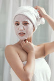 Facial mask for the young lady at spa. A young lady enjoying facial mask at spa, at beauty salon, indoors Stock Photo