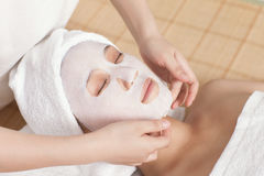Facial mask for the young lady at spa. At spa salon, Indoors Royalty Free Stock Images