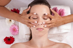 Facial massage. Pretty brunette lying in a spa salon and getting a facial massage Stock Photos